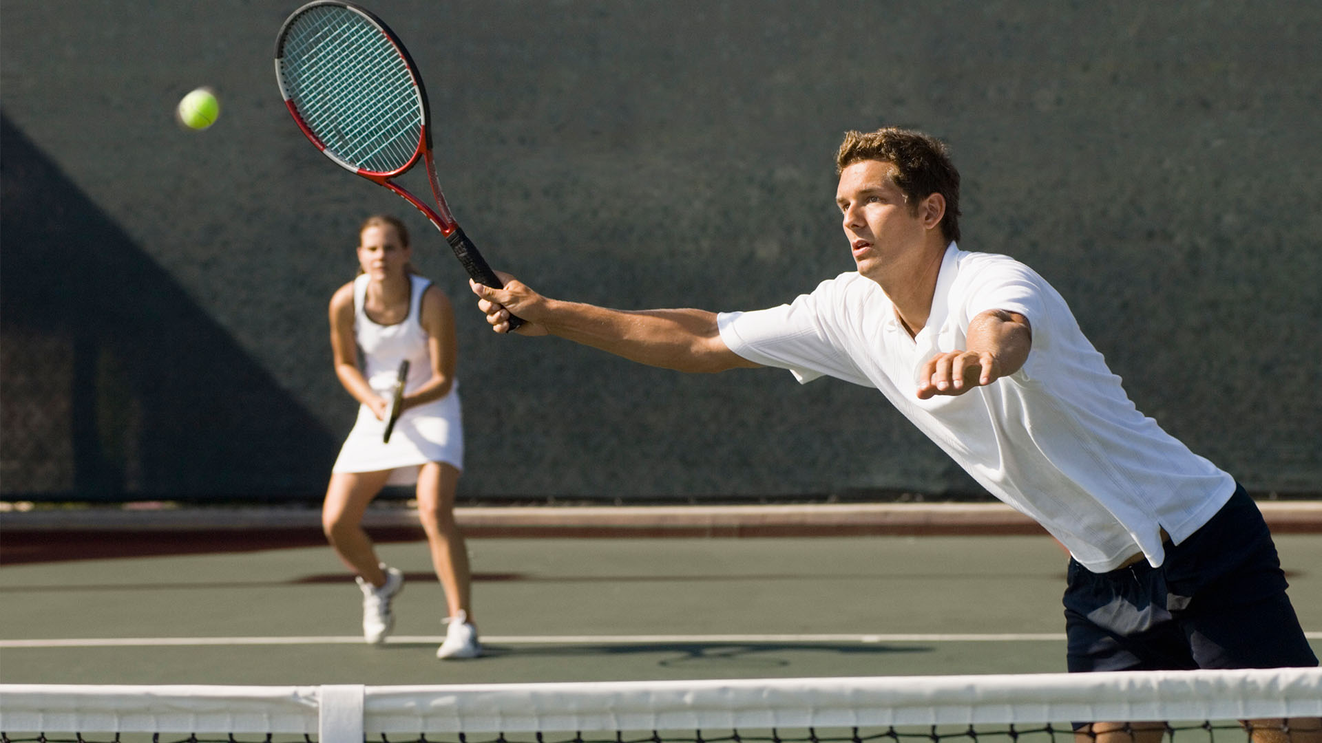 Mixed doubles tennis players with male reaching to hit a ball