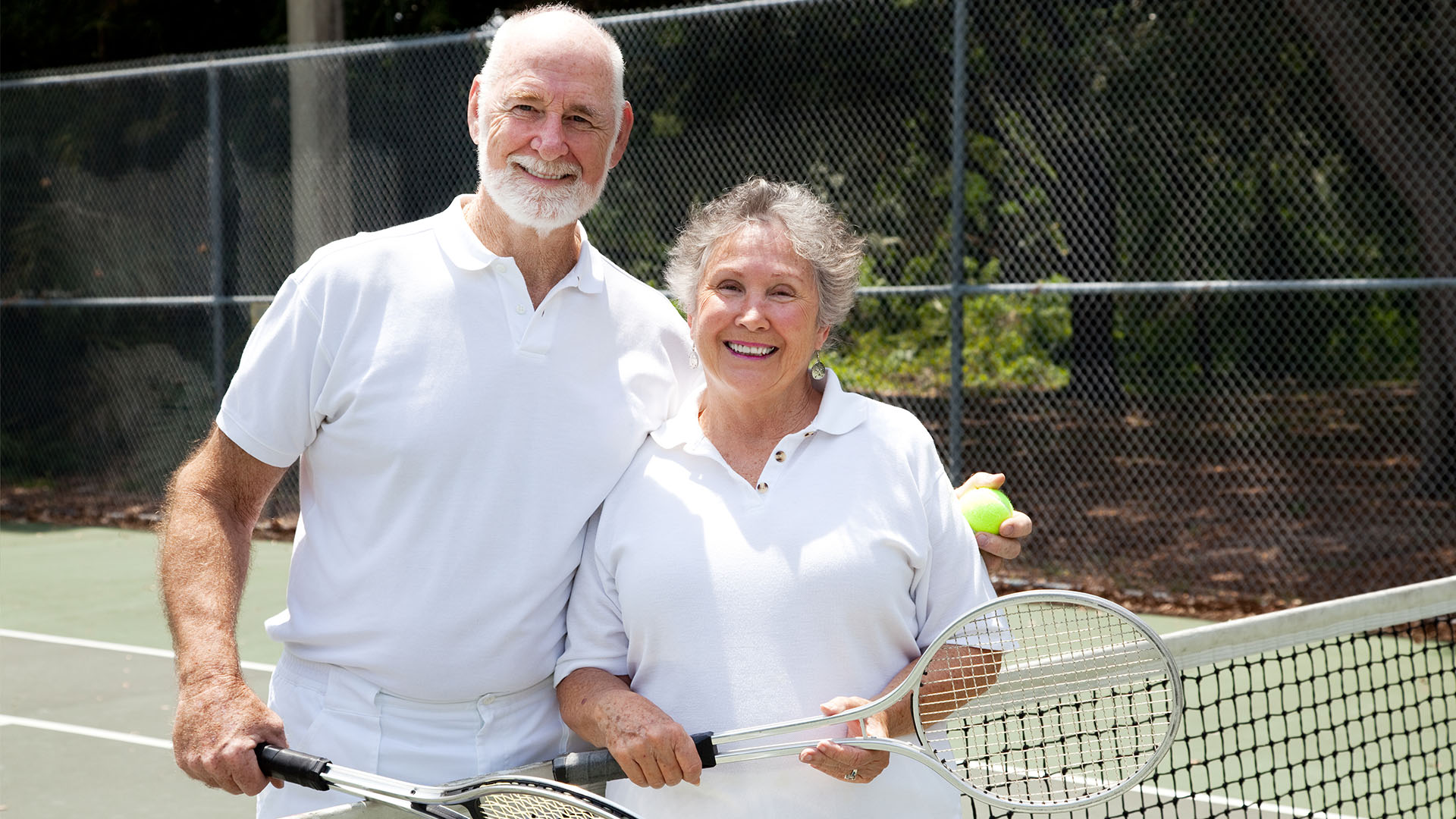 Male and Female senior tennis players next to net